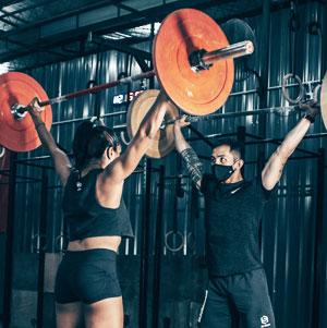 woman and man lifting weights
